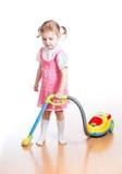 Scherzi la stanza di pulizia e del gioco con l'aspirapolvere del giocattolo Fotografia Stock
