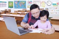 Scherzi lo studio con il suo istitutore nell'aula Fotografie Stock