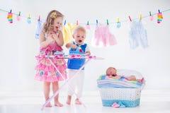 Scherzt bügelnde Kleidung für Babybruder Stockbild