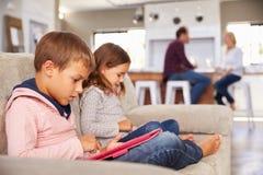 Scherzt das Spielen mit neuer Technologie, während Erwachsene unterhalten stockfotografie