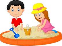 Scherzt die Karikatur, die auf dem Strand spielt, der eine Sandburgdekoration errichtet Stockfoto