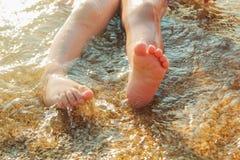 Scherzt Füße auf dem Strand im Wasser Stockfoto
