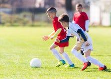 Scherzt Fußballfußball - Kinderspieler passen auf Fußballplatz zusammen Stockfotografie