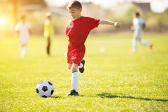 Scherzt Fußballfußball - Kinderspieler passen auf Fußballplatz zusammen Stockbild