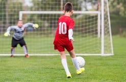 Scherzt Fußballfußball - Kinderspieler passen auf Fußballplatz zusammen Stockfotos