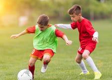 Scherzt Fußballfußball - Kinderspieler passen auf Fußballplatz zusammen Lizenzfreie Stockfotos