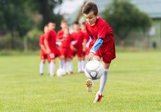 Scherzt Fußballfußball - Kinderspieler passen auf Fußballplatz zusammen Lizenzfreies Stockfoto