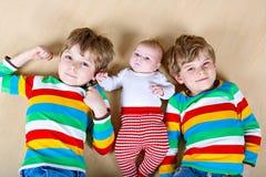 Scherzt glückliche kleine Vorschule zwei Jungen mit neugeborenem Baby Lizenzfreie Stockfotos