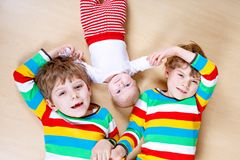 Scherzt glückliche kleine Vorschule zwei Jungen mit neugeborenem Baby Stockfotografie