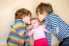Scherzt glückliche kleine Vorschule zwei Jungen mit neugeborenem Baby Stockbilder