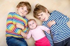 Scherzt glückliche kleine Vorschule zwei Jungen mit neugeborenem Baby Lizenzfreie Stockbilder