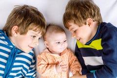 Scherzt glückliche kleine Vorschule zwei Jungen mit neugeborenem Baby Lizenzfreie Stockfotografie