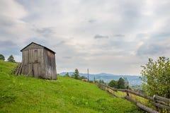 Scheune auf grünem Gras in den Bergen Stockfotos
