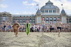First day of the new year dive 2018. SCHEVENINGEN, 1 January 2018 - Dutch people following the strong tradition of the first new year dive run toward the frozen royalty free stock photography