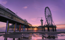 The Scheveningen pier. Pier of Scheveningen at sunset. Purple and orange colours in the sky are reflected in the water in the foreground. The pier hosts a Stock Photos