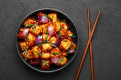 Free Schezwan Paneer In Black Bowl At Dark Slate Background. Schezwan Paneer Is Indo-chinese Cuisine Dish Royalty Free Stock Image - 161151376