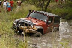 Schiacciamento Jeep Rubicon arancio che attraversa stagno fangoso Immagini Stock