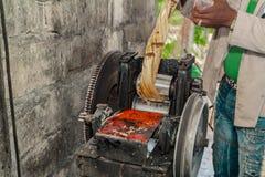 Schiacciando il succo dalla stampa manuale della canna da zucchero Fotografie Stock