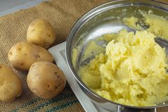 Schiacciando le patate bollite con uno schiacciapatate casalingo immagine stock libera da diritti