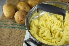 Schiacciando le patate bollite con uno schiacciapatate casalingo fotografia stock libera da diritti
