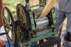 Schiacciando succo dalla canna da zucchero Facendo uso del meccanismo manuale per quello fotografie stock libere da diritti