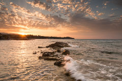 Schiacciare ondeggia sulle rocce dentellate durante il tramonto Fotografia Stock Libera da Diritti