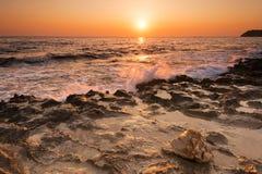 Schiacciare ondeggia sulle rocce dentellate durante l'alba immagini stock libere da diritti