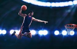 Schiacciata acrobatica di un giocatore del canestro nel canestro allo stadio fotografie stock libere da diritti