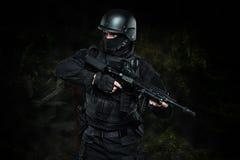SCHIAFFO dell'ufficiale di polizia dei ops di spec. nello studio dell'uniforme del nero fotografie stock