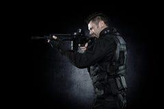 SCHIAFFO dell'ufficiale di polizia dei ops di spec. nello studio dell'uniforme del nero immagini stock