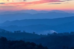 Schicht Berge im Nebel zur Sonnenuntergangzeit mit brennendem Himmel, lizenzfreies stockbild