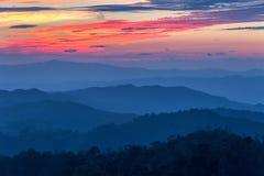 Schicht Berge im Nebel zur Sonnenuntergangzeit mit brennendem Himmel, stockfotografie