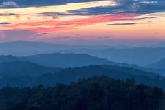 Schicht Berge im Nebel zur Sonnenuntergangzeit mit brennendem Himmel, lizenzfreie stockfotografie