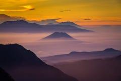 Schicht Berge und Nebel zur Sonnenuntergangzeit stockfotografie