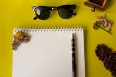 Schicht-Kaffeebohnen der Draufsicht flache, grinded Bohnen in der hölzernen Kaffeemühle der Weinlese, Weißbuch, Stift und Sonnenb stockbild