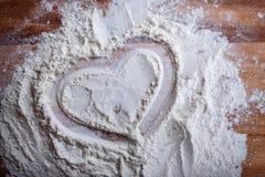 Schicht Mehl, zum des Herzens auf einem Schneidebrett zu zeichnen Lizenzfreie Stockbilder