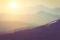 Schichten Berg und Dunst in den Tälern Fantastischer Abend, der durch Sonnenlicht glüht Stockbild