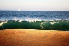 Schichten des Himmels, des Wassers, der Welle und des Sandes. Lizenzfreies Stockfoto