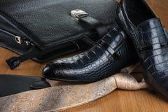 Schicke klassische blaue Schuhe, Bindung, Geldbeutel und Aktenkoffer auf dem Bretterboden Lizenzfreie Stockfotografie