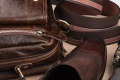 Schicke klassische braune Schuhe, Gurt, Regenschirm und Aktenkoffer auf dem Bretterboden Stockfotografie