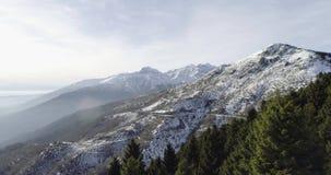 Schicken Sie Luftbrummenflug establisher über schneebedecktem Waldholz mit Bergen im Winter nach Schnee in der Gebirgsnatur stock video footage