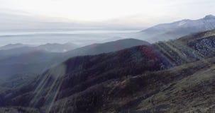 Schicken Sie Luftbrummenflug establisher über Waldholz mit Bergen und Flugzeugen im Winter nach Schnee im Berg-natur stock video