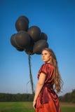 Schicker Verlust im roten Kleid mit schwarzen Ballonen über blauem Himmel Stockbild