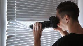 Schießen des Spions 4K, der Paparazzi oder des Detektivs auf Kamera durch die Jalousien stock video