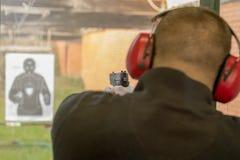 Schießen mit einer Pistole Mann-Zündungspistole im Schießstand lizenzfreie stockfotografie