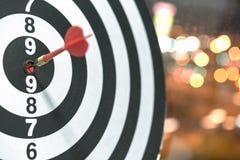 Schießen Sie den Zielpfeil, der auf Bullauge mit bokeh Hintergrund schlägt Lizenzfreie Stockfotografie