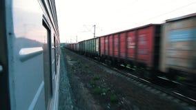 Schießen von einem beweglichen Zug In der entgegengesetzten Richtung auf den benachbarten überschreitenen BahnGüterzug stock video