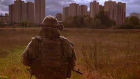 Schießen von hinten, gehenden Soldaten in der Tarnung, führt zu die Wolkenkratzer und hält Gewehr, der Überfahrtweg, dunkel stock footage