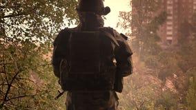 Schießen von hinten, Schattenbildsoldaten in der Tarnung, die gerade steht und voran von Ziegelstein verlassenem Gebäude schaut stock video