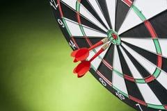 Schießt die Pfeile, welche die Zielmitte auf einem grünen Hintergrund schlagen Stockfotografie